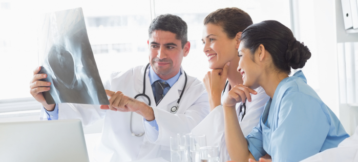 http://www.dreamstime.com/stock-photos-smiling-medical-team-analyzing-xray-hospital-image37816293